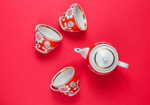 Xícaras de cerâmica retrô e bule isolados em vermelho