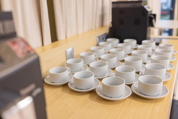 Xícaras de chá branco vazias em cima da mesa.