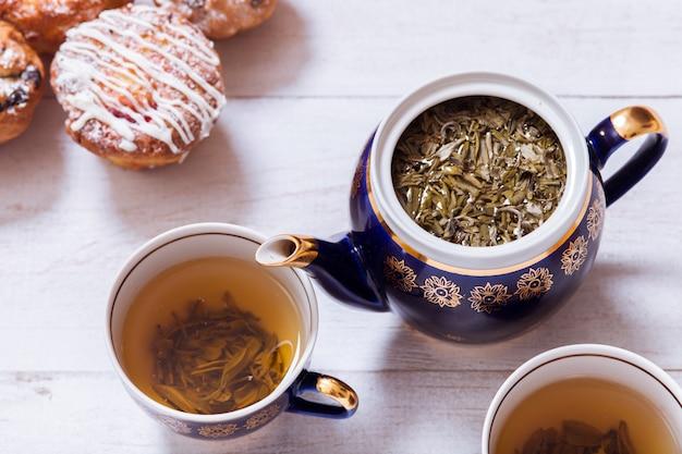 Xícaras de chá, bule e muffins na mesa de madeira branca, top close-up vista