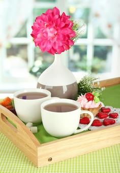 Xícaras de chá com flores e bolo na bandeja de madeira na mesa da sala