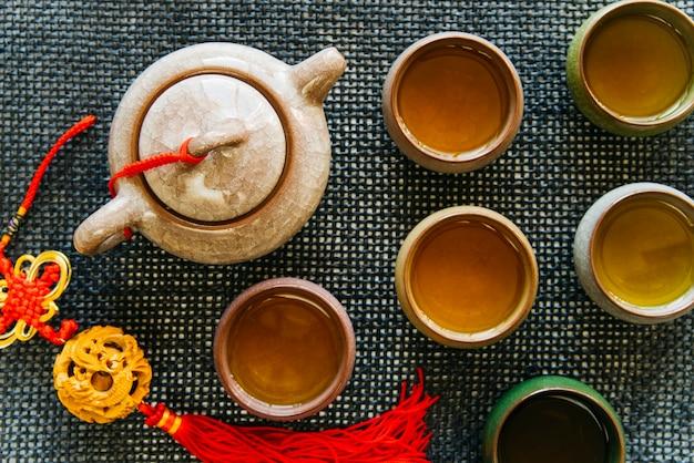 Xícaras de chá de cerâmica e bule com borla no placemat