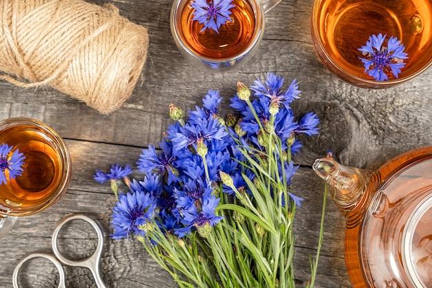 Xícaras de chá de ervas, bule transparente e flores de centáurea azuis na superfície da madeira