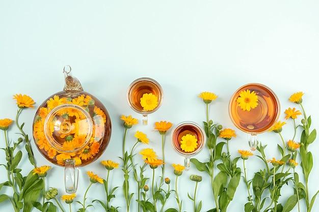 Xícaras de chá de ervas e bule transparente com flores de calêndula sobre fundo azul. o chá de calêndula beneficia o seu conceito de saúde. vista superior flat lay copy space.