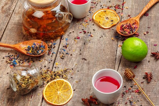 Xícaras de chá de ervas saudável com canela, rosa seca e camomila flores em colheres sobre fundo de madeira, vista superior