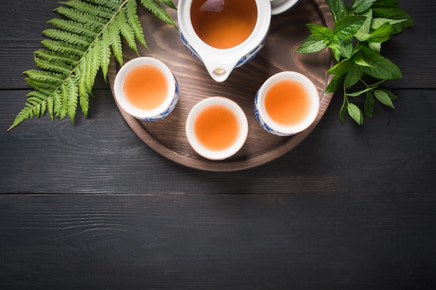 Xícaras de chá e chaleira em fundo escuro