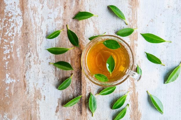 Xícaras de chá e folhas de chá fresco em uma mesa de madeira