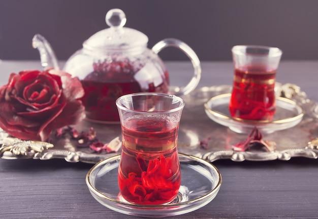 Xícaras de chá karkade vermelho quente com bule na bandeja