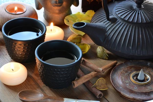 Xícaras de chá preto acompanhadas de incenso, canela e velas