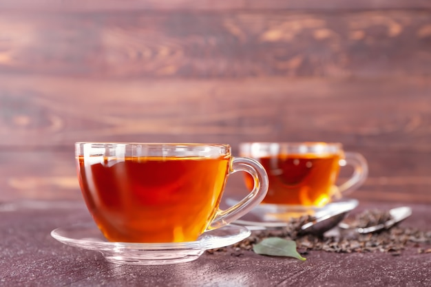Xícaras de chá quente em fundo de madeira