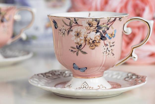 Xícaras de chá rosa com ornamento floral e doces de biscoito
