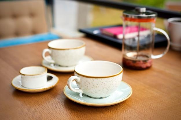 Xícaras de chá vazias e bule na mesa de madeira em um café com terraço