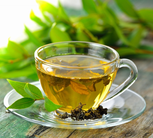 Xícaras de chá verde na mesa sobre fundo de madeira