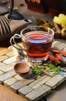 Xícaras de chá vermelho acompanhadas de incenso, canela e velas