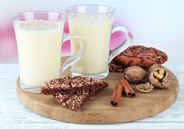 Xícaras de gemada com canela e biscoitos na mesa no fundo brilhante