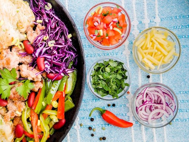 Xícaras de legumes perto de prato mexicano