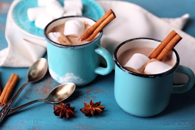 Xícaras de saboroso chocolate quente, na mesa de madeira,