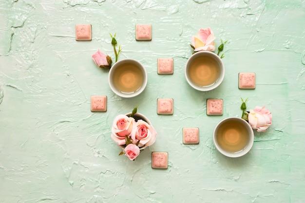 Xícaras de turquesa com chá de rosas, flores de rosas, chocolate rosa com menta