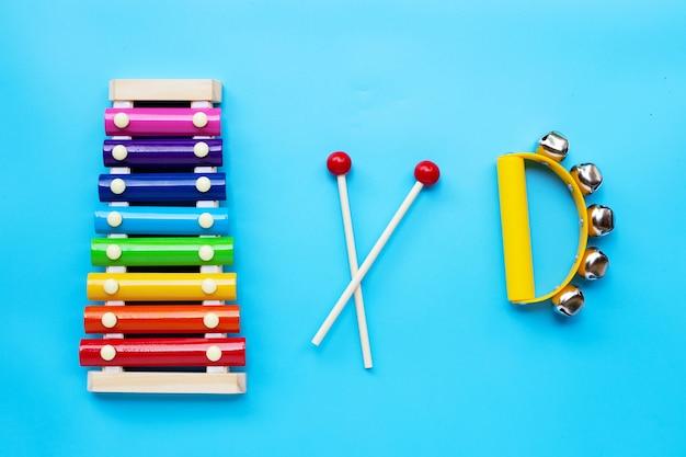 Xilofone colorido com instrumento musical de sinos de mão para tocar na superfície azul. vista do topo