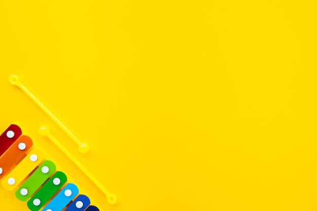 Xilofone infantil de arco-íris brilhante sobre um fundo amarelo.