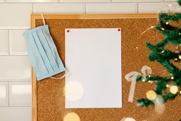Xmas cópia espaço em branco folha de papel em placa de cortiça máscara médica árvore de ano novo e luzes bokeh