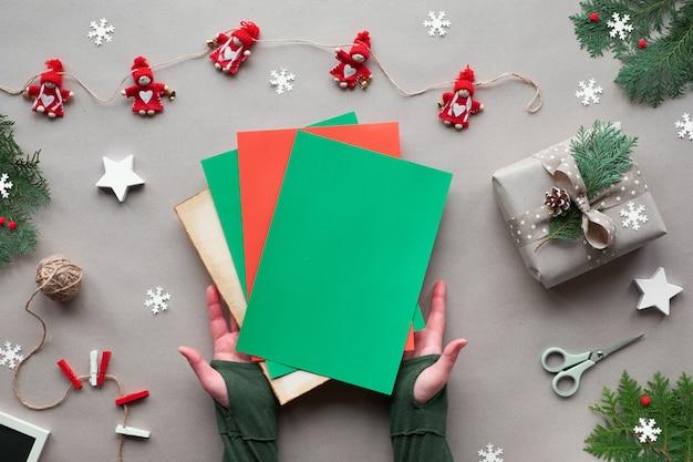 `xmas eco amigável alternativa. zero resíduos natal, configuração plana, vista superior em fundo de papel ofício - guirlanda têxtil, estrela, mãos segurar papel de cor com cópia-espaço, lugar para o seu texto.