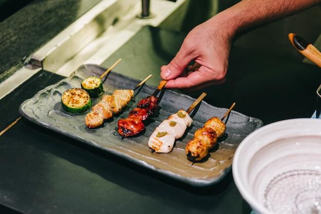 Yakitori (espetos de frango grelhado em estilo japonês) com frango, órgão interno e pepino.