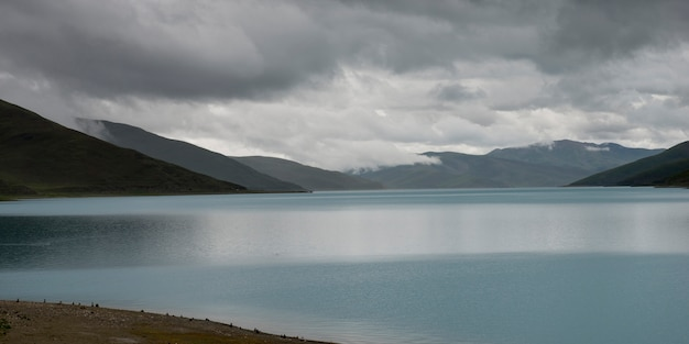 Yamdrok lago com montanhas sob céu nublado, nagarze, shannan, tibete, china