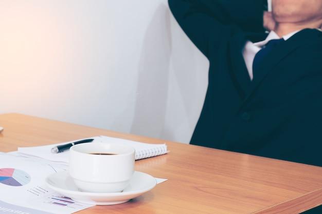 Yang empresário relaxando em sua mesa no escritório com as mãos cruzadas atrás da cabeça e os olhos fechados