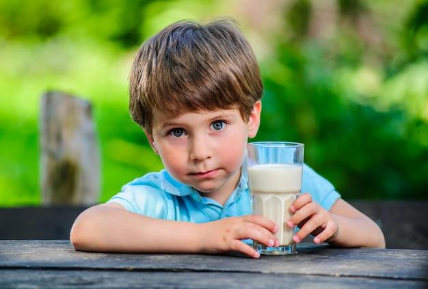 Yang pequeno e bonito menino retratado com copo de leite.