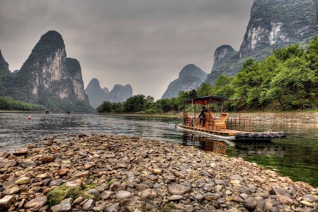 Yangshuo, guangxi, china tourist riverboat navigating, li river tour, lijiang river cruise em guilin, sul da china, destinos turísticos populares nas férias de guilin.