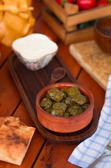Yarpag dolmasi, yaprak sarmasi, folhas de uva verdes recheadas com arroz e carne na tigela de cerâmica com iogurte.