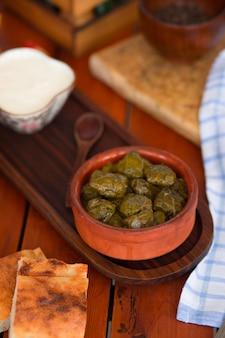 Yarpag dolmasi, yaprak sarmasi, folhas de uva verdes recheadas com arroz e carne na tigela de cerâmica.