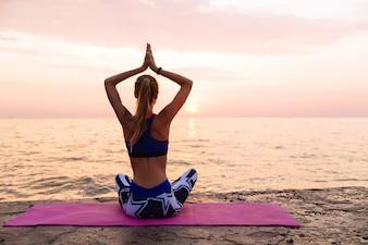 Yoga ao nascer do sol. mulher esportiva, praticando ioga, sentado no cais em posição de lótus