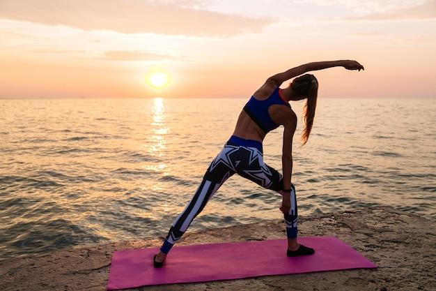 Yoga ao nascer do sol. vista traseira, de, sportive, mulher, fazendo, exercícios, para, corpo, prática, ioga