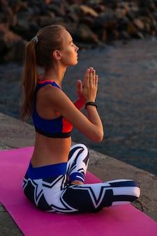 Yoga ao pôr do sol. vista lateral, de, mulher bonita, sentando, em, posição lotus, meditação