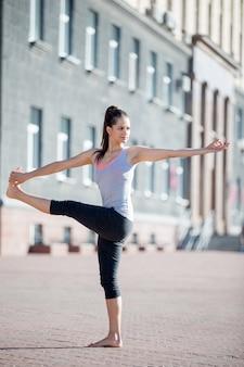 Yoga de rua: revolvido de mãos dadas para a pose do dedo grande