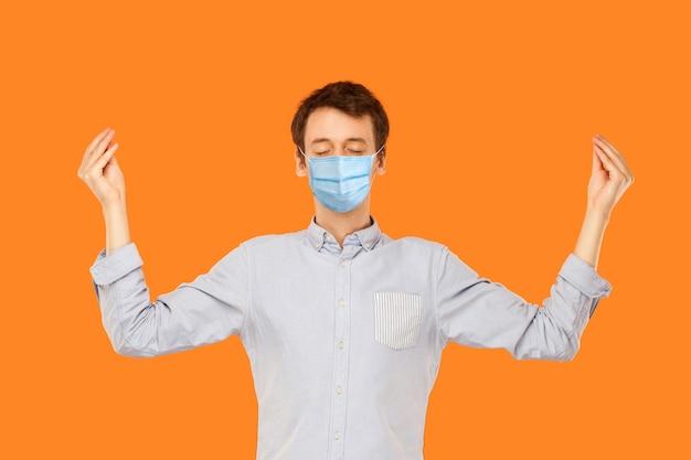 Yoga e meditação. retrato de homem jovem trabalhador calmo com máscara médica cirúrgica em pé com os olhos fechados e meditando. estúdio interno tiro isolado em fundo laranja.