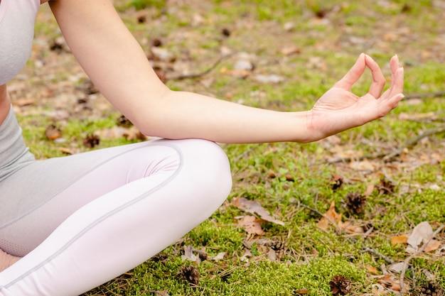 Yoga na floresta. close-up nas mãos. mulher jovem em roupas esportivas fazendo ioga ao ar livre na floresta