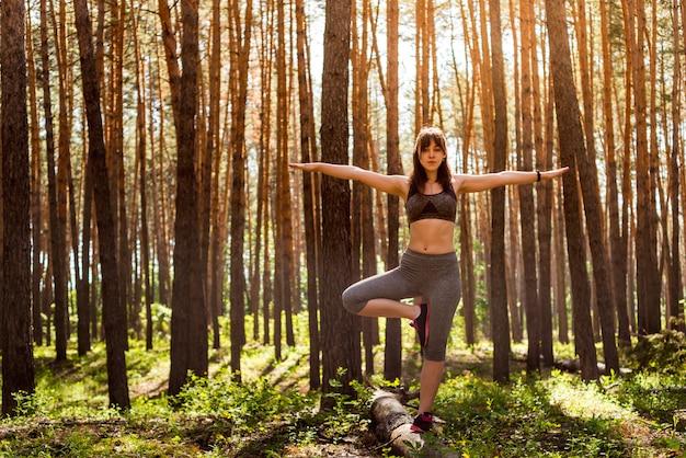 Yoga na floresta de manhã verão, ao ar livre com o efeito da luz.