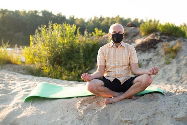 Yoga na praia. máscara vestindo do homem sênior na pose dos lótus que senta-se na areia. conceito de calma e meditação.
