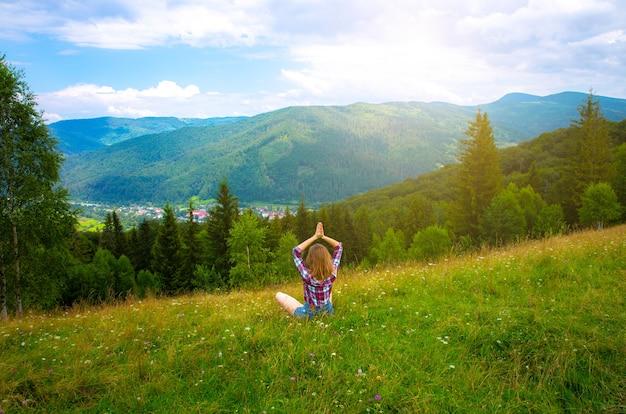 Yoga nas montanhas. linda garota está meditando em asana. natureza incrível ao redor. conceito de harmonia e desejo de viajar. hipster viajando. mulher elegante curtindo a vida.