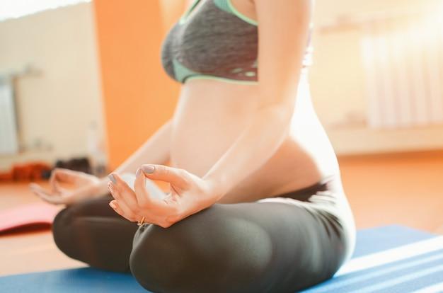 Yoga para mulheres grávidas. menina grávida nova que faz a ioga