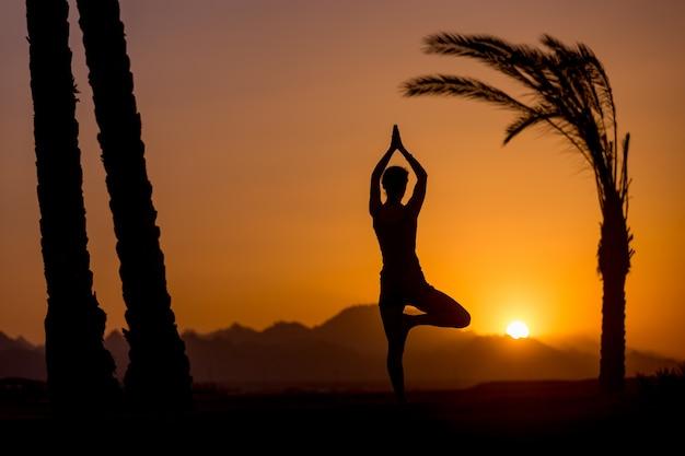 Yoga vrikshasana posa em local tropical