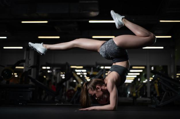 Yogi garota fazendo inversão avançada e braço-equilíbrio scorpion handstand.