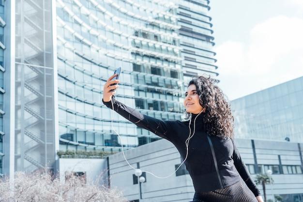 Yogi linda mulher praticando ioga e usando telefone celular