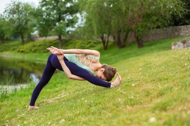 Yogi morena jovem e esbelta realiza exercícios de ioga desafiadores grama verde no verão no contexto da natureza