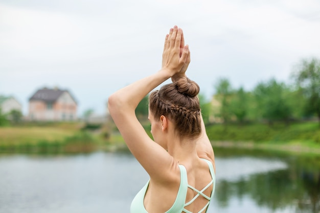 Yogi morena jovem e magro não executa exercícios de ioga complicados na grama verde no verão contra a natureza