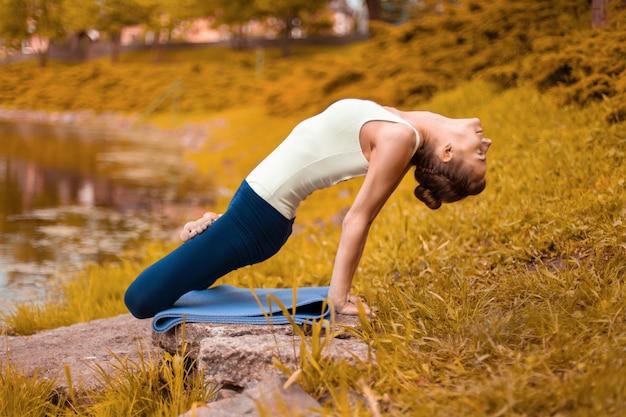 Yogi morena jovem esbelto executa exercícios de ioga desafiadores na grama verde.