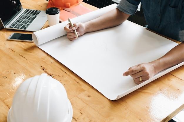 Yong, arquiteta, homem, trabalhando, com, desenhos técnicos, laptop, telefone, segurança, leme, e, coffe, copo