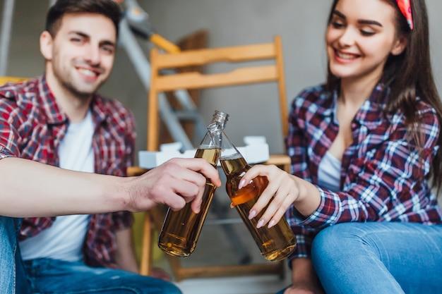 Yong casal bebendo cerveja em novos apartamentos
